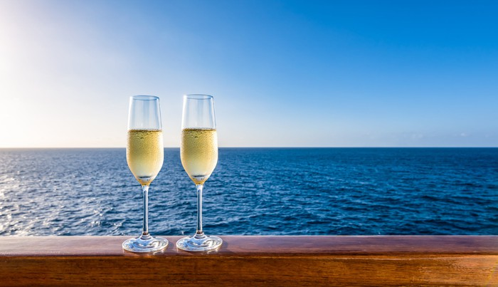 Two full champagne glasses resting on a railing with the ocean behind them.