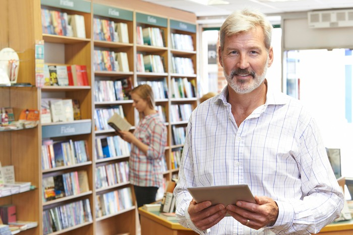 A man smiling in a bookstore