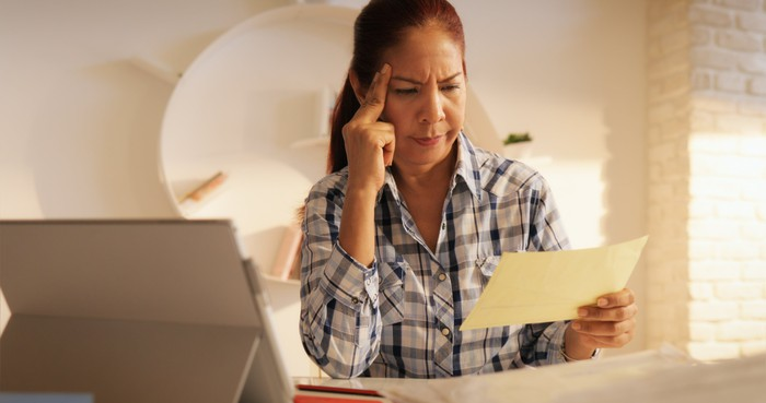 Woman looking at paper, unhappy.