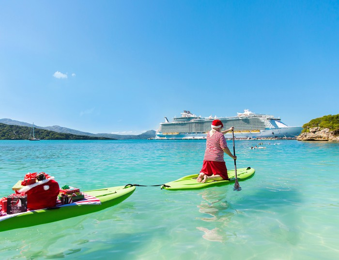 A costumed Santa Claus paddles towing presents as he approaches a Royal Caribbean ship.