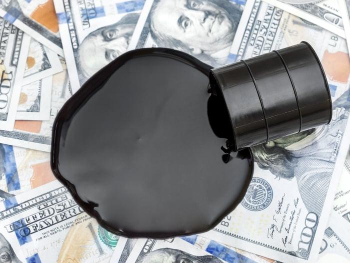 An oil drum spills black liquid onto a pile of $100 bills.