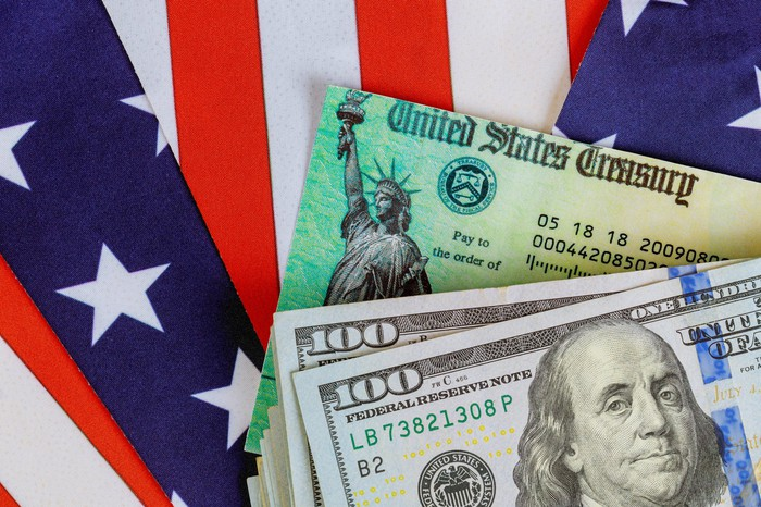 A messy stack of one hundred dollar bills, and a U.S. Treasury check lying atop a partially folded American flag.