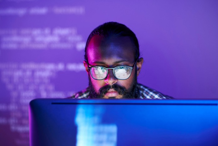 Young man in glasses looks  at a desktop screen in  a dark room lit with purple light.