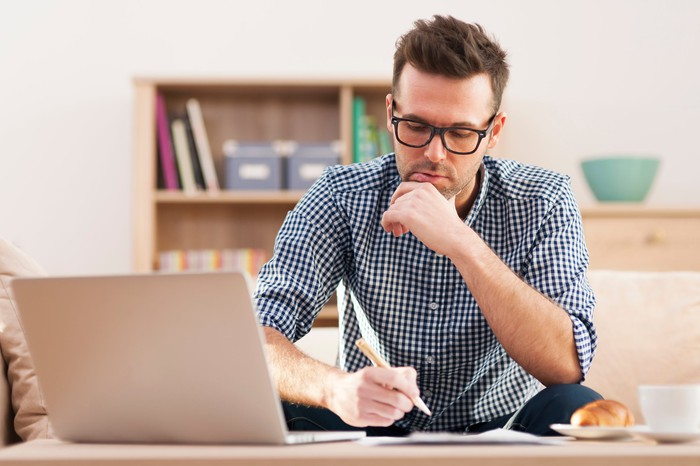 A man making notes as he looks at material on his laptop