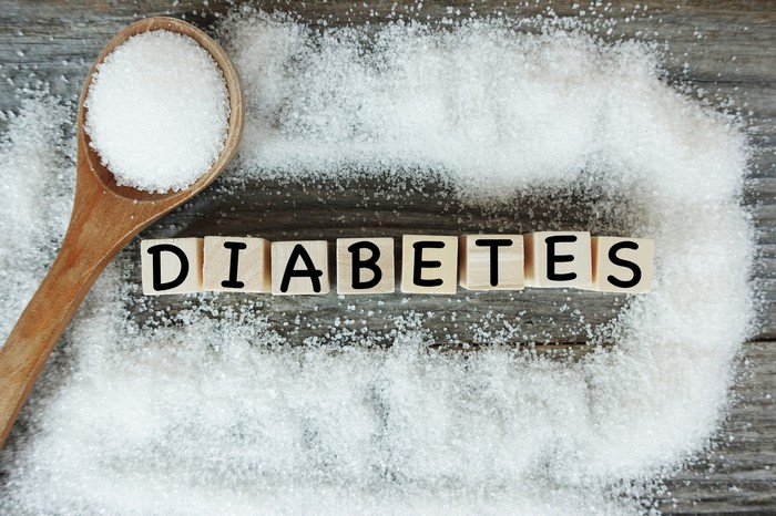 A wooden spoon pouring sugar on a wooden table around a set of wooden blocks that spell the word diabetes