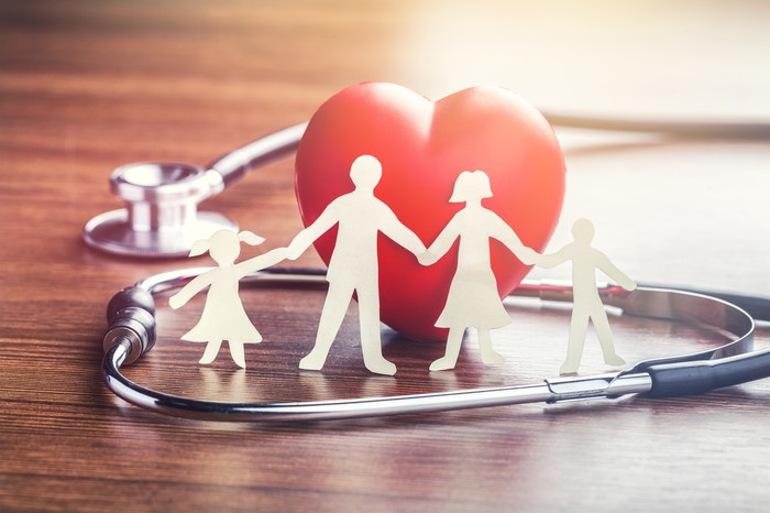 A paper cutout of a family holding hands with a heart in the background and a stethscope.