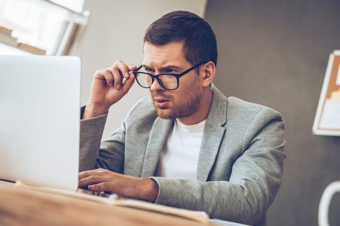 Man at laptop adjusting glasses
