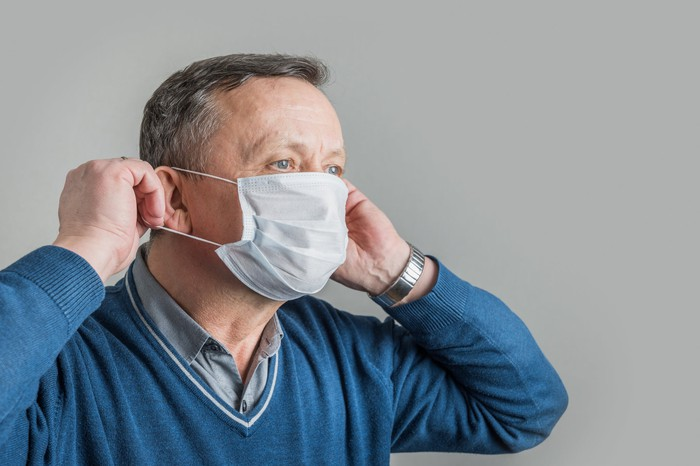 A man putting on a medical face mask