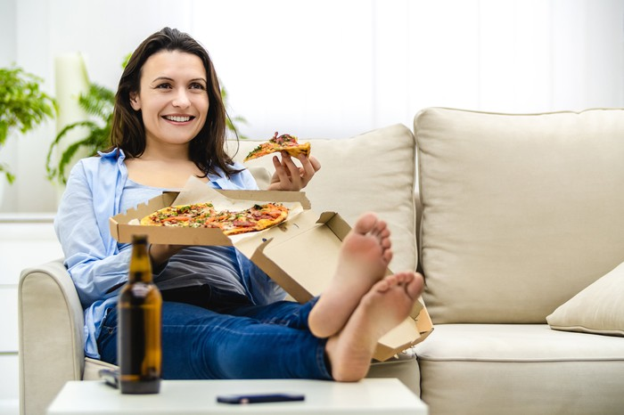 A woman eating pizza on her couch at home