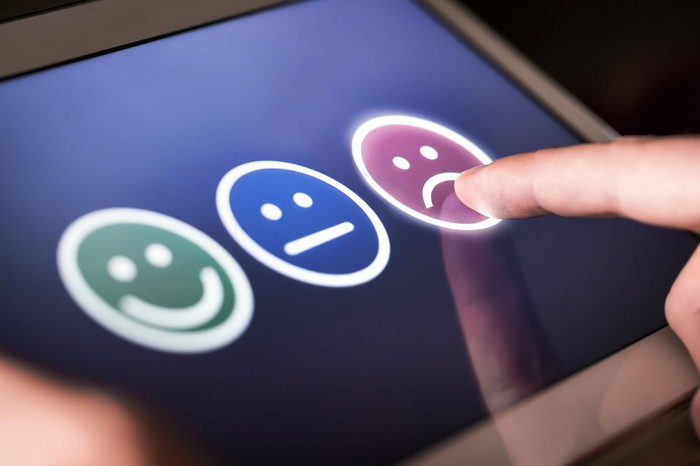 Finger pointing to frown emoji on touchscreen