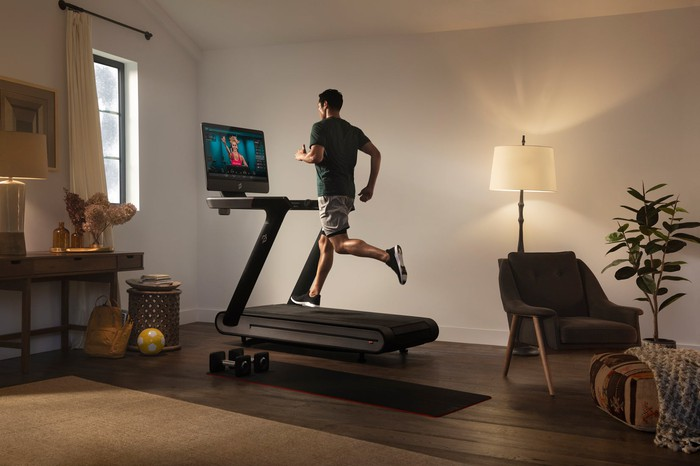 Man running on a Peloton treadmill in a home.