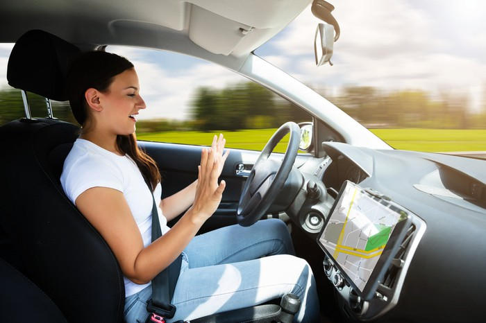 A woman lets go of the steering wheel in a driverless vehicle.