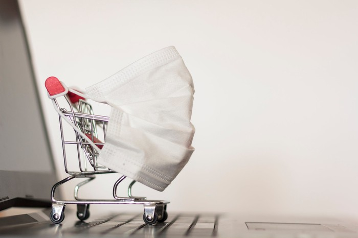 A mini shopping cart with a face mask on it is shown on the keyboard of a laptop.