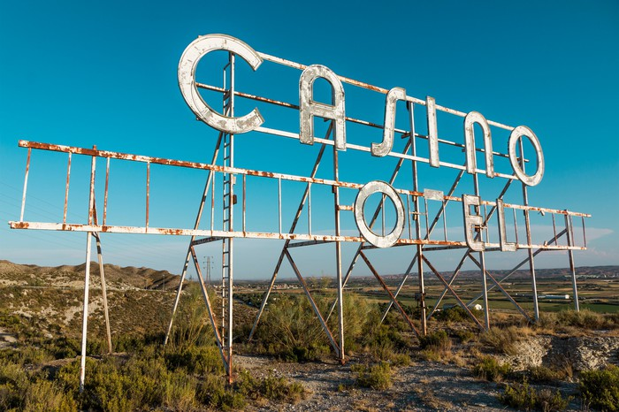 A dilapidated casino sign with an open field behind it