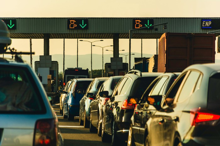 Lines of cars at a highway toll booth.