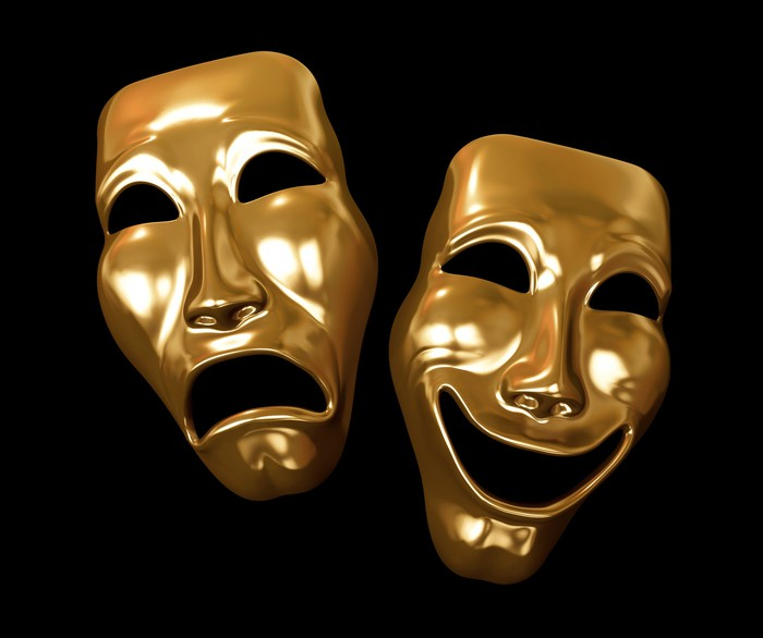 Golden tragedy and comedy masks, resting on a black backdrop.