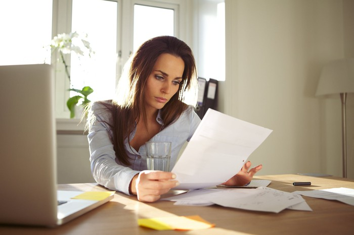 A woman looking at financial documents in front of her laptop