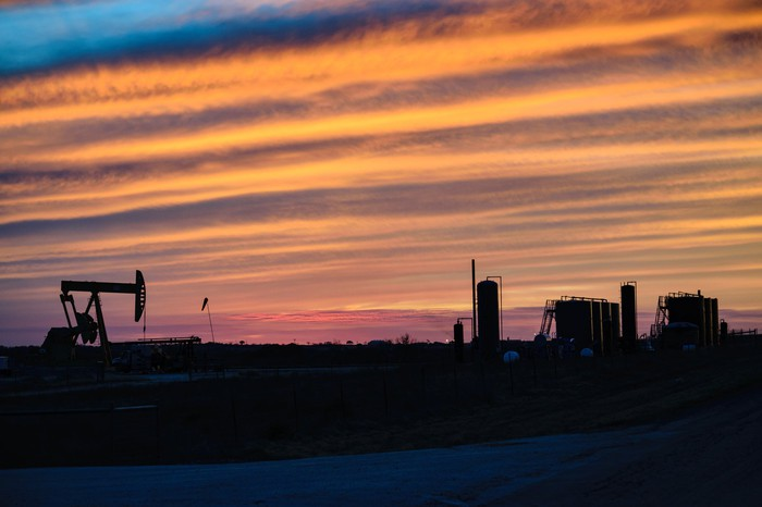 An oil pump at dusk with rows of clouds in the sky.