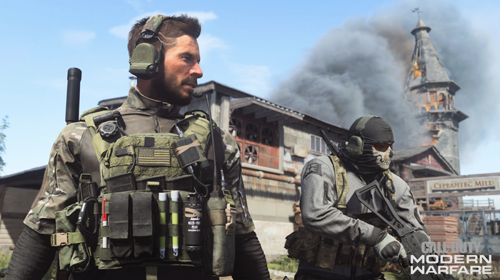 A screenshot of Call of Duty Modern Warfare showing two soldiers standing in an industrial area with a building on fire in the background.