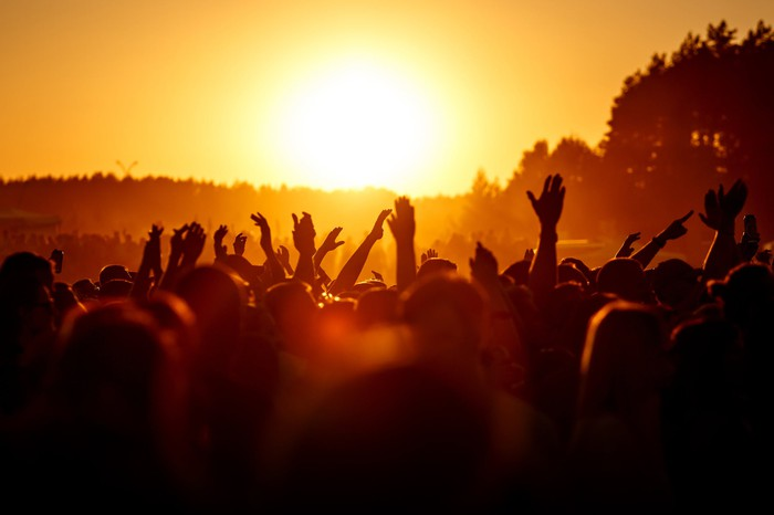 People at a concert with their hands in the air as the sun sets in the background