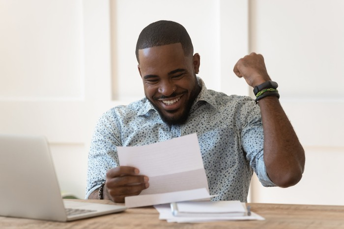 Man reading letter and pumping fist in joy