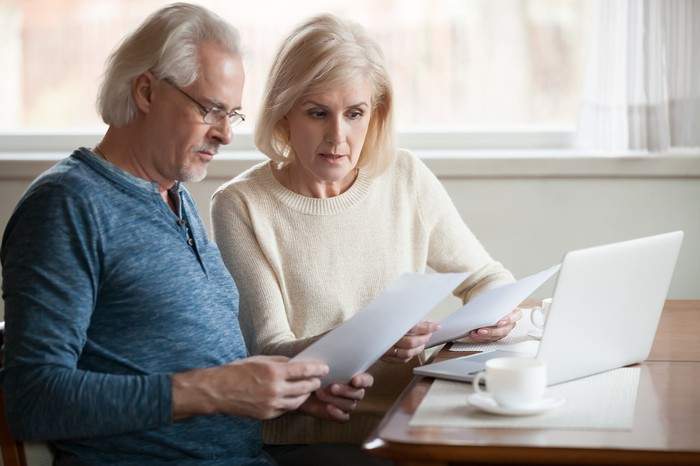 Older man and woman sitting at laptop holding documents