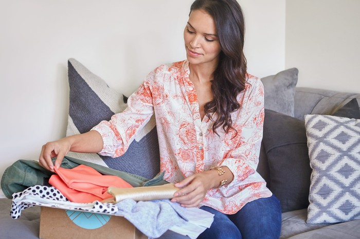 Woman opening Stitch Fix box of clothes on a couch