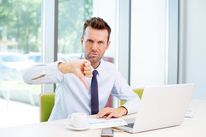 Man at laptop giving thumbs down sign