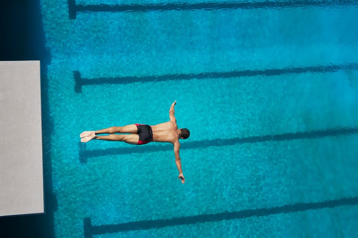 Man diving from a platform into a pool.