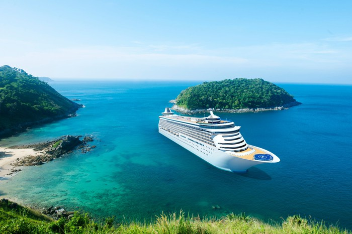 A cruise ships docks in a small bay in a tropical  setting.