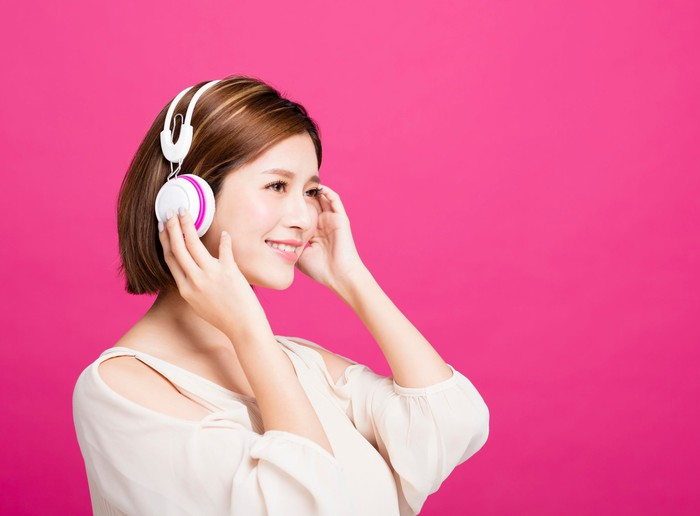 A young woman listens to music on her headphones.