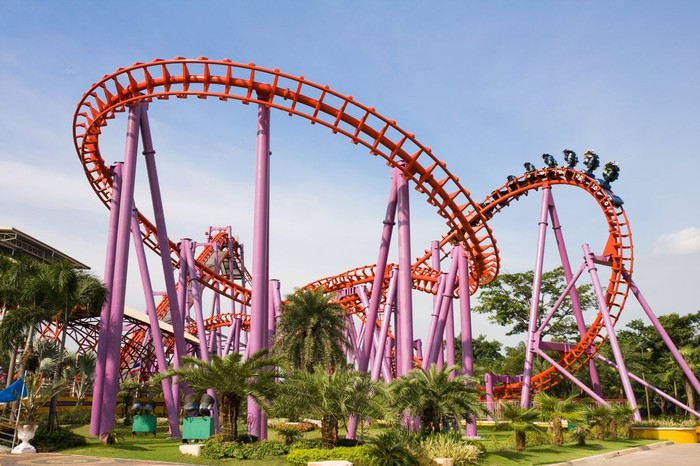 A pink and red roller coaster surrounded by tropical vegetation