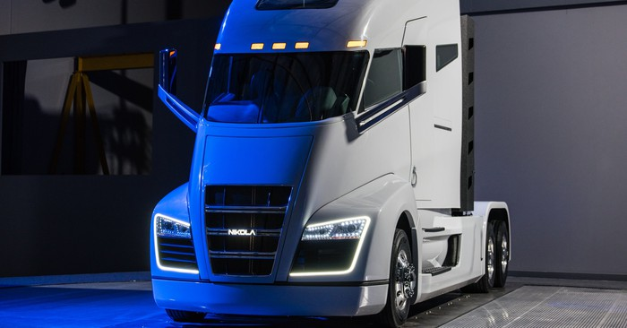 A while Nikola One semi truck, parked in a garage and illuminated by blue light.
