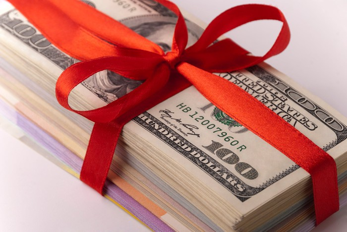 Stack of bills wrapped in a red bow