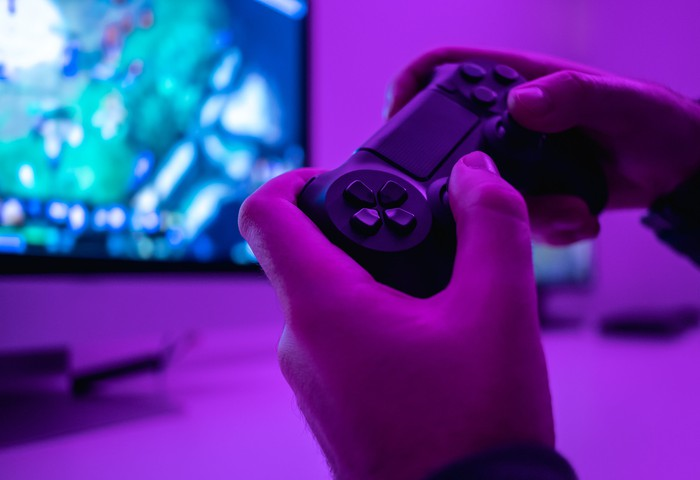 Someone holding a video game controller with a TV screen in the background.