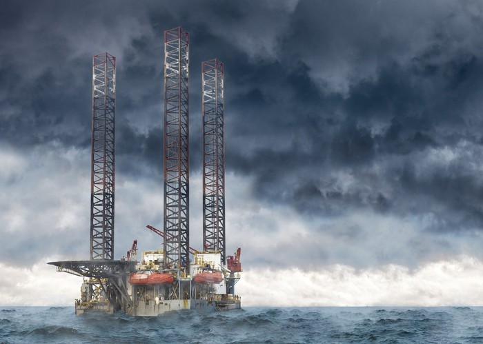 An offshore drilling platform with cloudy skies in the background
