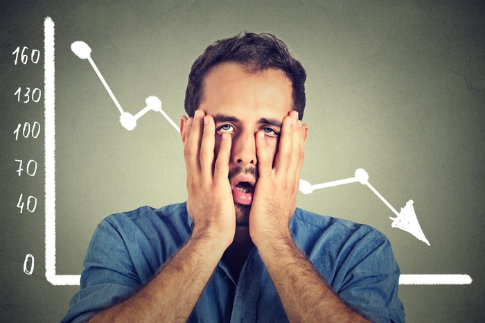 A man holding his face in front of a chart going down