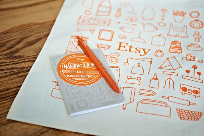 Etsy-branded pen and notebook on top of a wood table.