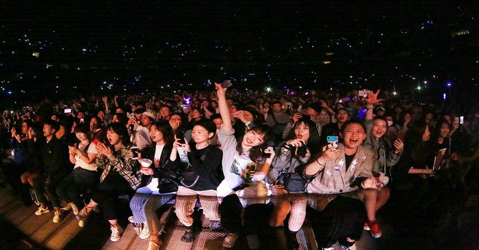 A crowd in the front rows of a live music event.