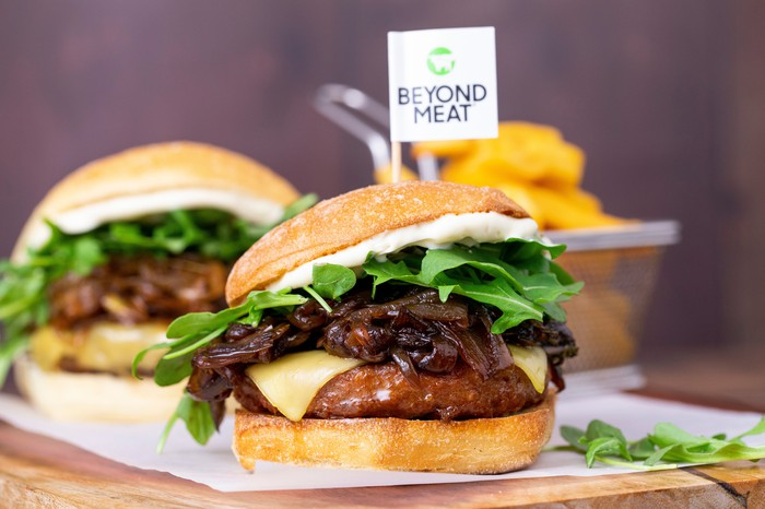 Two Beyond Burgers with cheese, onions, spinach, and a white sauce in buns sitting on a white cloth on a wood surface.