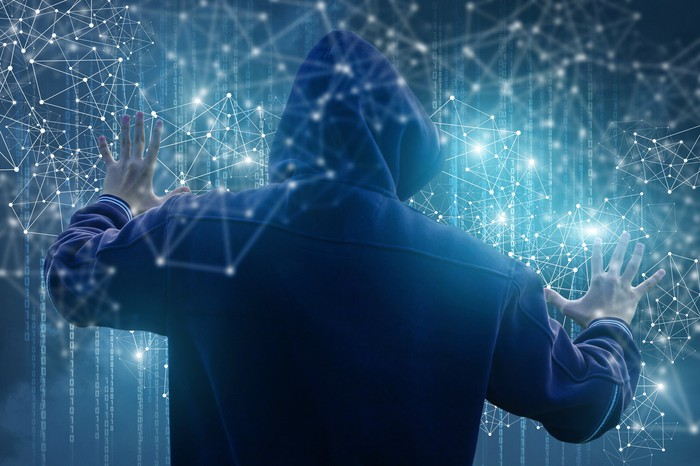 A hooded hacker reaches out into a web of network connections.