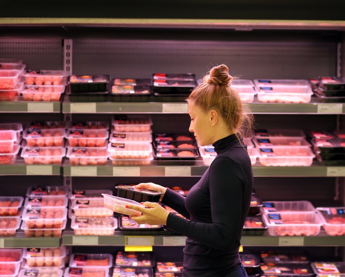 A woman shops in the meat section of a supermarket.