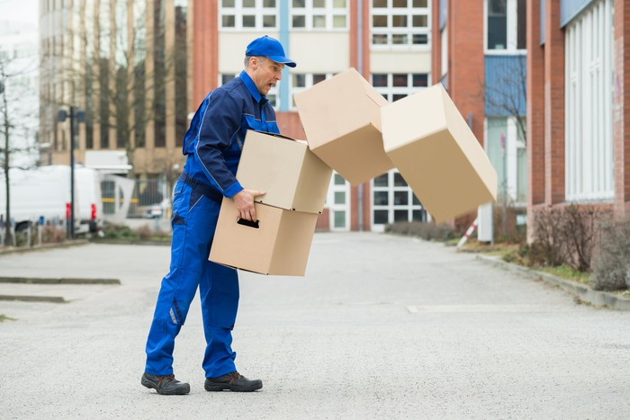 Uniformed delivery man standing on a sidewalk and reacting in surprise as the boxes he's carrying are tumbling out of his grasp.