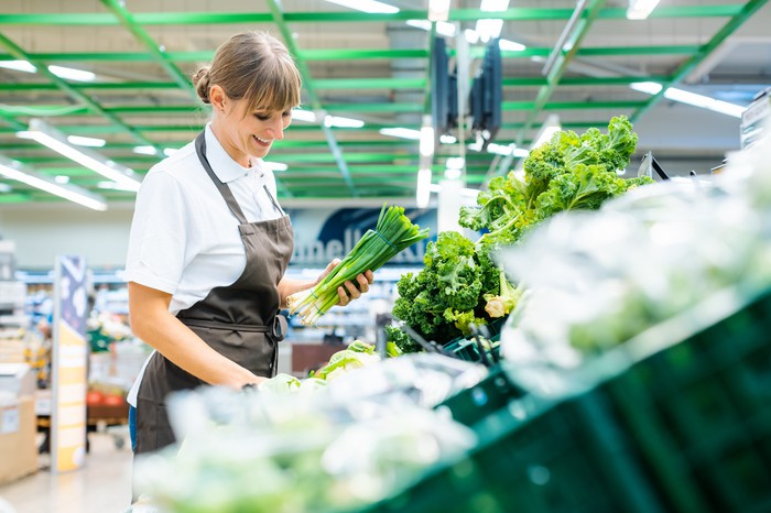 A grocery employee restocking vegetables.