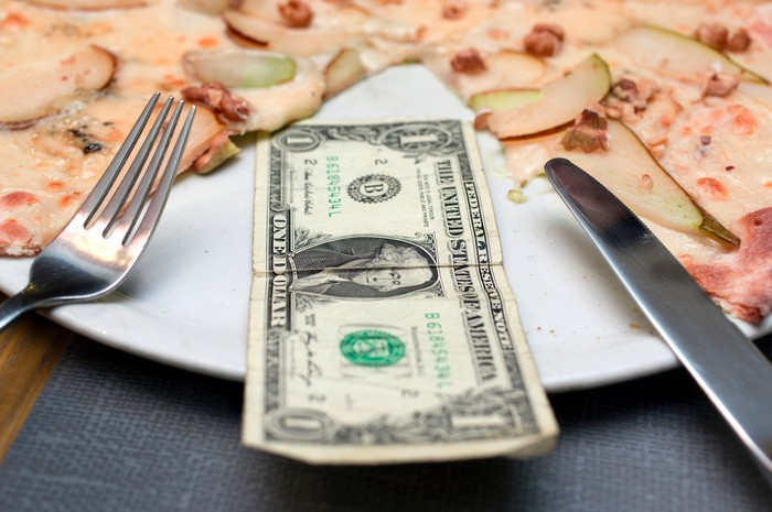 Pizza pie with a one-dollar bill in place of one slice.