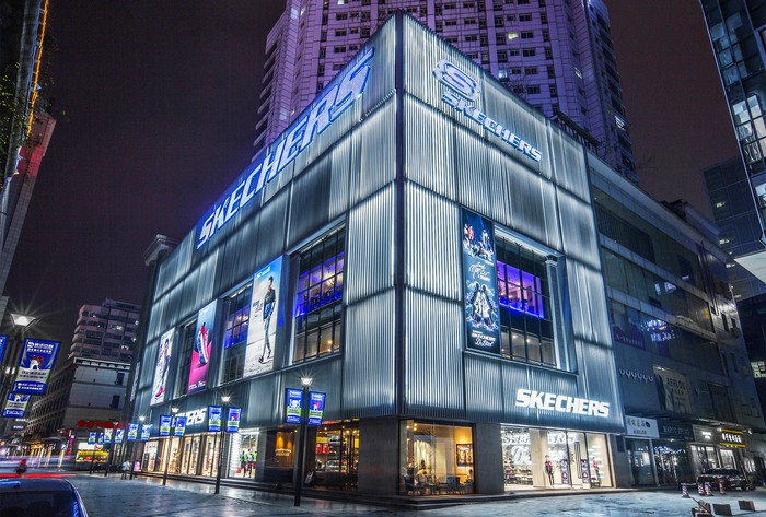 A Skechers retail store front in China. Skyscrapers can be seen rising behind the store.