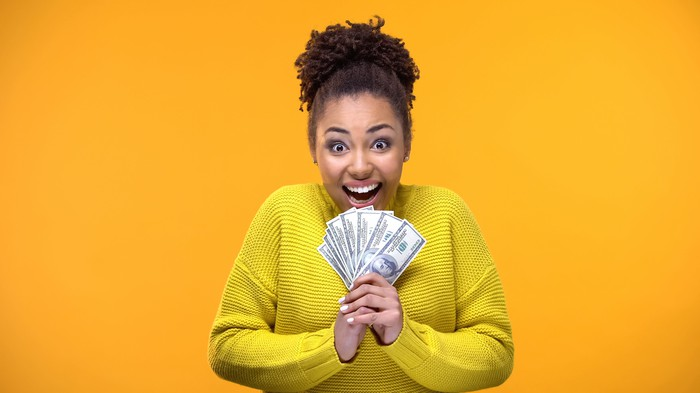 A smiling woman holds a fan of $100 bills.