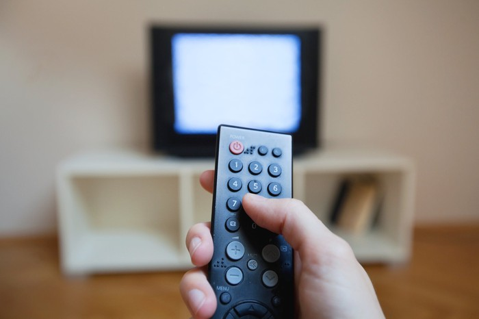 Closeup on a hand holding a television remote with a static-filled TV in the background.