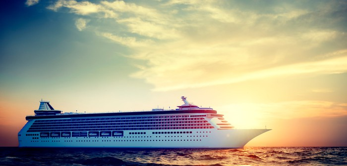 A cruise ship sailing in the ocean with the sun shining behind it.