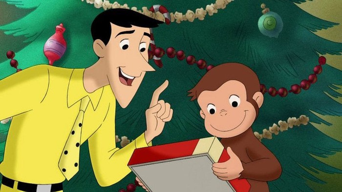 Curious George and character known as The Man with the Yellow Hat stand in front of Christmas tree and ornaments.